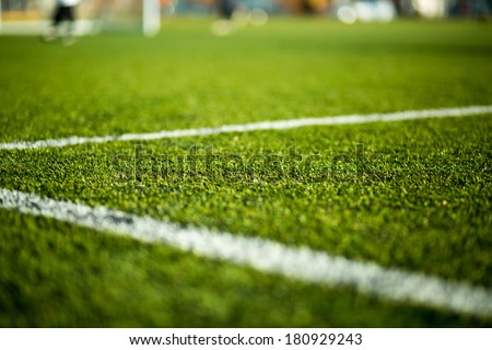 Close-up of artificial turf. Blurred legs of soccer players in the background. - stock photo