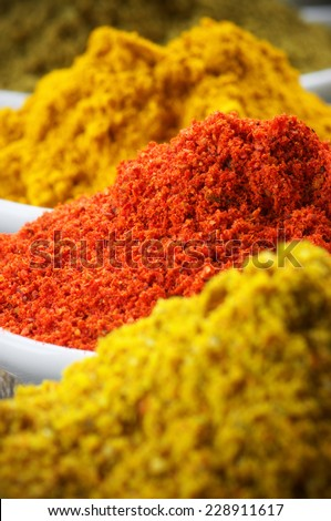 Close-up of assorted powder spices: curry, paprika and turmeric. Shallow DOF. - stock photo