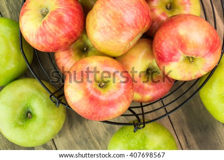 Close up of assorted ripe apples in a basket and wooden background. - stock photo