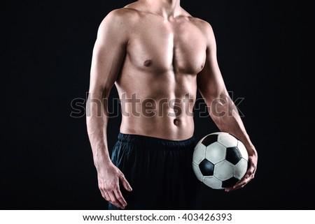 Close up of attractive and muscular football player. Studio shot of young shirtless sportsman on black background. Man with football ball - stock photo