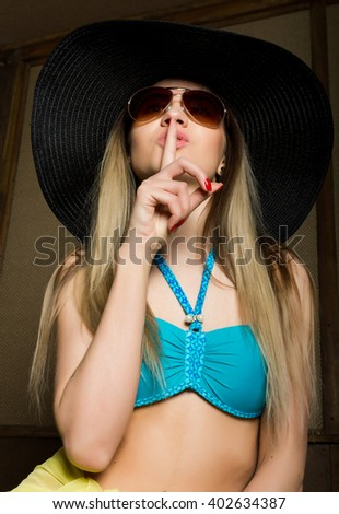 Close-up of attractive brunette woman in a bikini, big hat and sunglasses putting a finger on her lips - stock photo