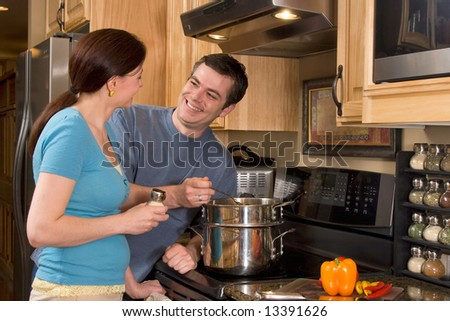 Close up of attractive couple standing in the kitchen by the stove and smiling at each other. Horizontally framed shot. - stock photo