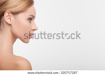 Close up of attractive girl standing in profile. She is looking forward with confidence. Her shoulders are naked. Isolated and copy space in right side - stock photo