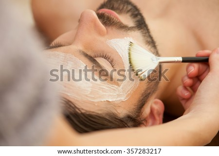 Close up of attractive man lying and relaxing at spa. The beautician is applying facial cream on his skin - stock photo
