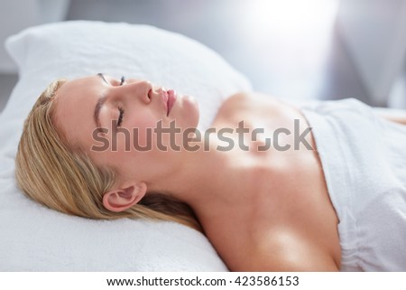 Close up of attractive woman at dayspa. She is lying on massage table. Beauty and health concept. - stock photo
