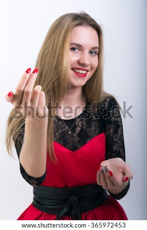 Close-up of attractive woman making hand gesture beckoning - stock photo