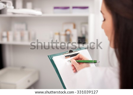 Close up of attractive young expert beautician scheduling next appointment. The woman is holding a folder of papers and writing with concentration. She is standing in her office - stock photo