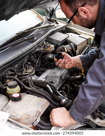 Close up of auto mechanic opens the oil cap - stock photo