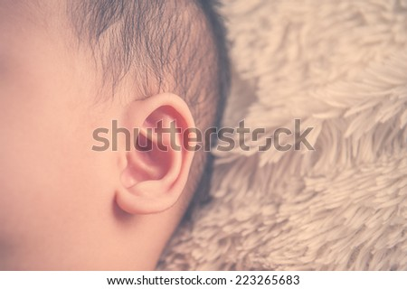 close up of baby ear. Vintage color - stock photo