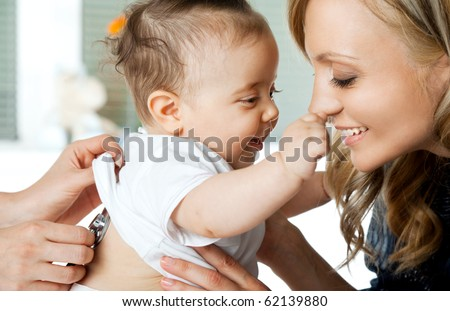Close-up of baby girl being examined by doctor, playing with mother - stock photo