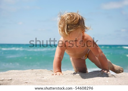 close up of baby on sand beach - stock photo