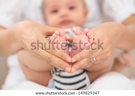Close-up of baby�¢??s feet in mother�¢??s hands - stock photo