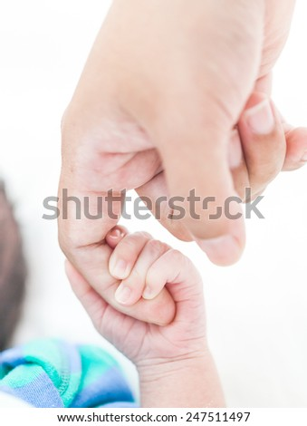 Close-up of baby's hand holding mother's finger - stock photo