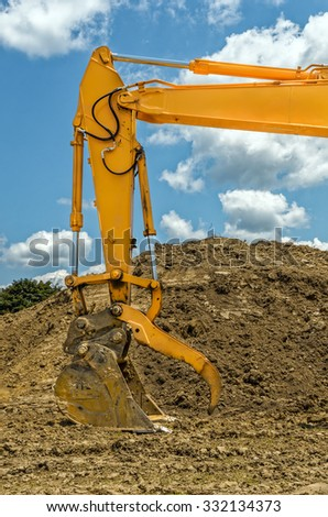 Close up of Backhoe Scooping Up Soil at a Construction Site - stock photo