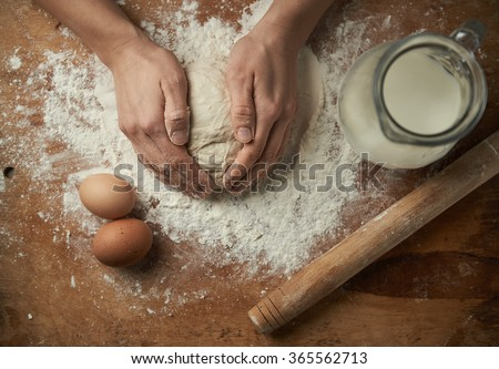 Close-up of baker hands kneading cake dough on the board with flour, eggs and milk. Baking concept. - stock photo