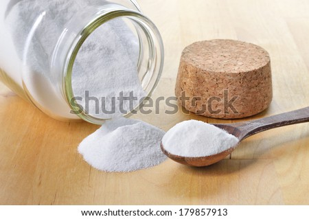 Close-up of baking soda in a glass jar. Bicarbonate of soda. - stock photo