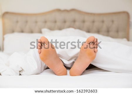 Close up of bare feet in bed at home - stock photo