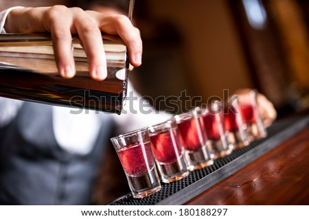 close-up of barman hand pouring alcohol into shot glasses in a nightclub or bar - stock photo