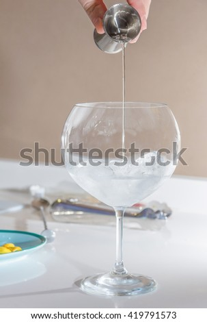 Close up of barman hand pouring alcoholic drink with a jigger on glass to prepare gin tonic cocktail - stock photo
