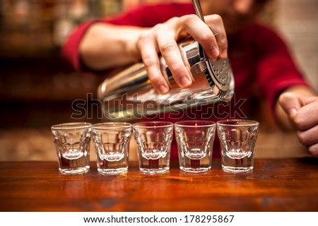Close-up of bartender hand pouring alcoholic drink in nightclub, pub or bar - stock photo