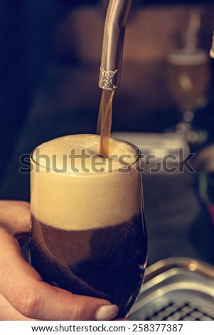 Close Up Of Bartender Hands Pouring Dark Beer Into Glass - stock photo