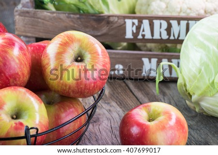 Close up of basket with ripe apples and farmers crate with cabbage in the background. - stock photo
