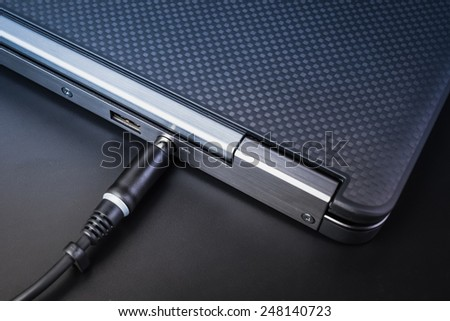 close up of battery charge on laptop computer with power plug - stock photo