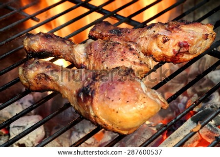 Close-up Of BBQ Chicken Legs On The Hot Flaming Charcoal Grill In The Background - stock photo