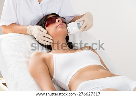Close-up Of Beautician Giving Epilation Laser Treatment On Woman's Face - stock photo