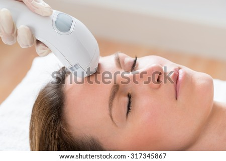 Close-up Of Beautician Giving Laser Epilation Treatment To Young Woman Face - stock photo