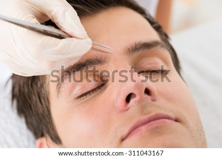 Close-up Of Beautician Hands Plucking Handsome Man Eyebrows With Tweezers - stock photo