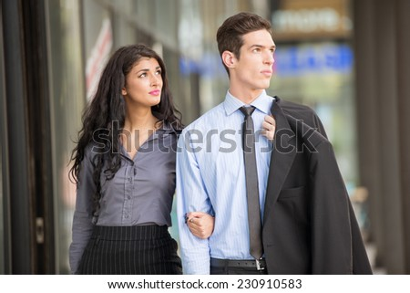 Close-up of beautiful and handsome pair of young men and women, elegantly dressed, photographed walking outside. - stock photo