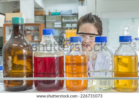 Close up of beautiful asian scientist looking at chemical bottle - stock photo