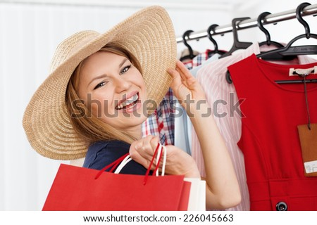 Close-up of beautiful blond lady choosing summer hat standing at clothes rack in shopping mall. Young happy smiling Caucasian woman buying accessories in small boutique.  - stock photo