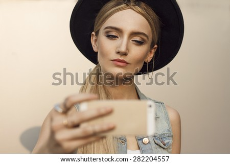 Close up of beautiful blonde woman with black hat. Take a self portrait with her smart phone. Wearing denim vest. Her hair is tied to ponytail. Selective focus on woman with shallow depth of field. - stock photo