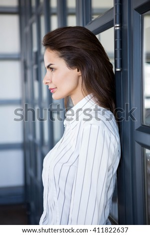 Close-up of beautiful businesswoman young leaning on office door - stock photo