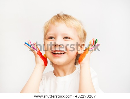 Close up of beautiful face of Caucasian little child. Baby boy with hands in paint. Portrait of happy blond boy isolated at white background. Close up of smiling face and hands of kid in color paint. - stock photo