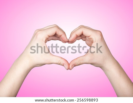 Close up of beautiful female hands form heart shape isolated on pink background - stock photo