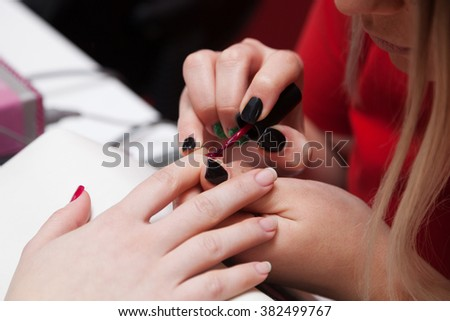 Close up of beautiful female hands having manicure treatment. Nail polishing. - stock photo