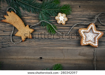 close-up of beautiful festive Christmas still life of the branches of spruce, cookies and spice on wood background with cracks studio - stock photo