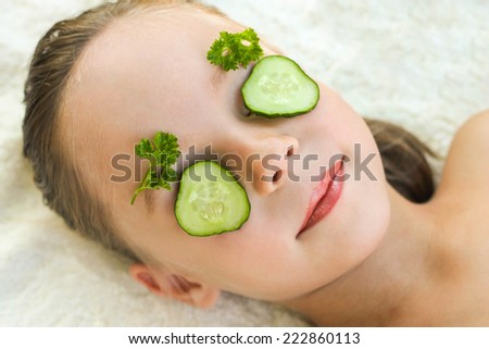 Close up of beautiful girl with facial mask of cucumber  - stock photo
