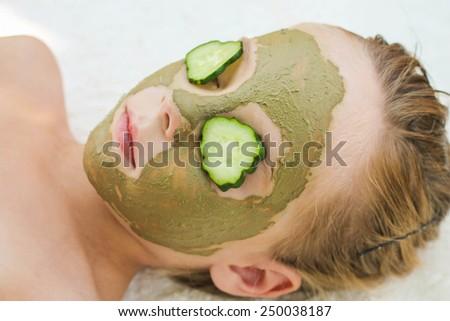 Close up of beautiful girl with facial mask of cucumber  - stock photo