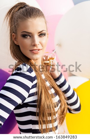 close-up of beautiful girl with smokey eye make up, ponytail hair in black and white striped dress with bunch of multicolored balloons - stock photo