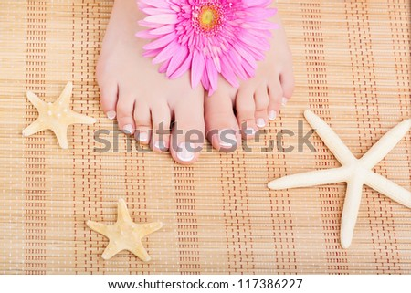 Close-up of beautiful manicured feet with a pedicure, flower and starfish - stock photo