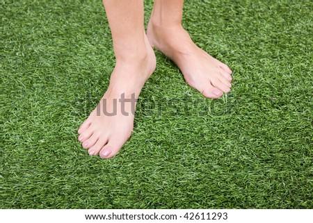 Close up of beautiful slim female feet on green grass - stock photo