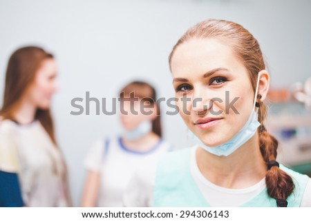 Close-up of beautiful woman dentist smiling cheerfully to camera with her assistant and patient talking on background - stock photo