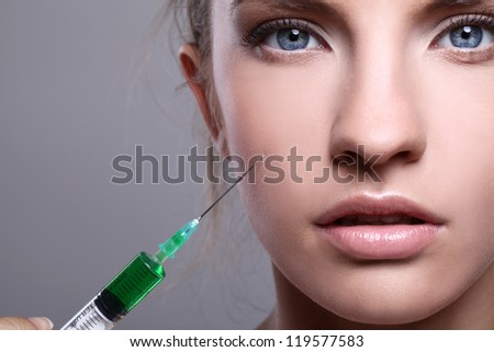 Close up of beautiful woman gets an injection in her face - stock photo