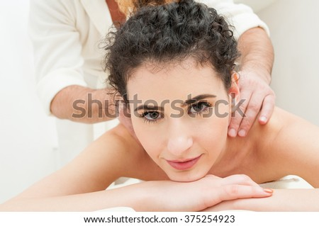 Close-up of beautiful woman getting massage in a spa center as resort and relaxation concept - stock photo