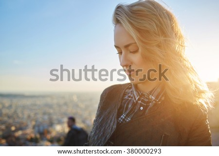 Close up of beautiful woman standing on a viewpoint against sky and sundown in warm spring evening, charming young female enjoying calm and rest after walking outdoors during her vacation holidays - stock photo