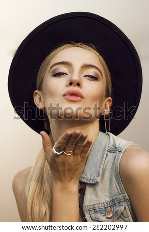 Close up of beautiful young  blonde woman sending a kiss . Wearing denim vest, necklace and white undershirt. Her hair is tied to ponytail. Professional make-up, hair style and styling. - stock photo